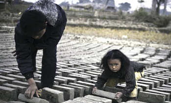 Bipana Tamang (4 years old) helps her dad turn bricks to dry in the sun. Photo: Alice Carfrae, © Legatum Limited 2014